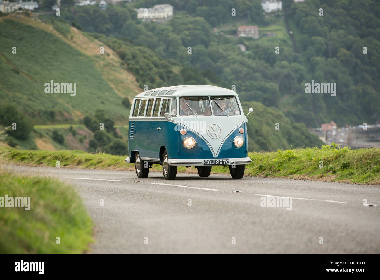 classic VW 1965 original British RHD 21 window caravette campervan travelling around the countryside, Devon, UK - Stock Image