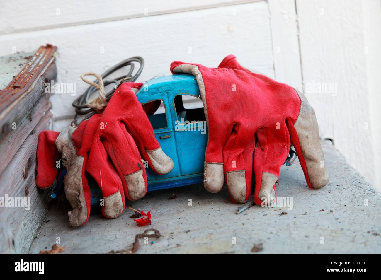 An old blue tin VW-beetle toy car lies abandoned on a shelf in a garden, covered with red garden gloves Stock Photo