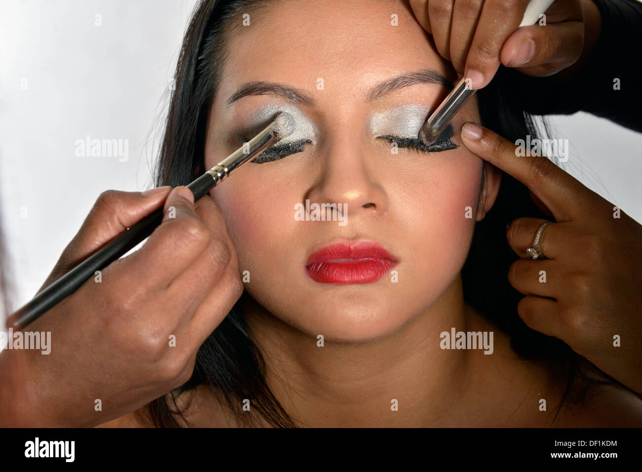 An asian woman having make-up applied - Stock Image