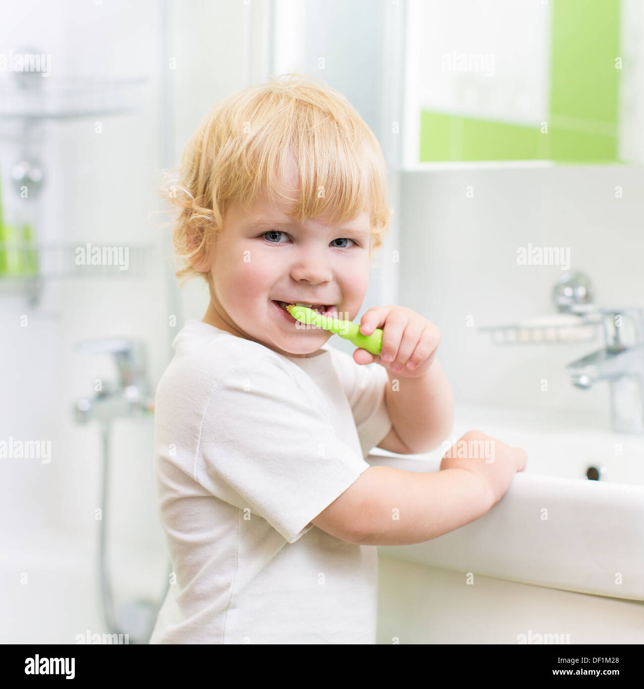Kid boy brushing teeth in bathroom - Stock Image