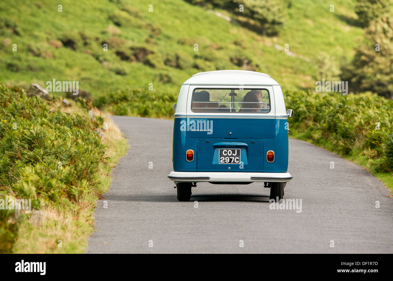 classic VW 1965 original British RHD 21 window caravette campervan travelling around the countryside, Devon, UK - Stock Image