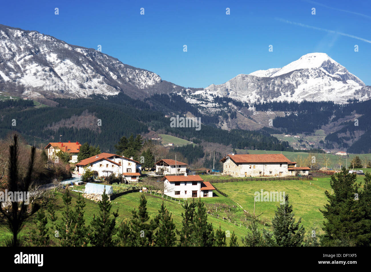 village in Aramaio valley, surrounding by snowy mountains, in Basque Country. Stock Photo