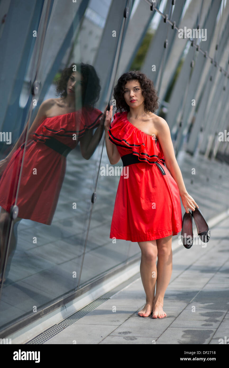 Woman in red dress touch angle glass wall - Stock Image