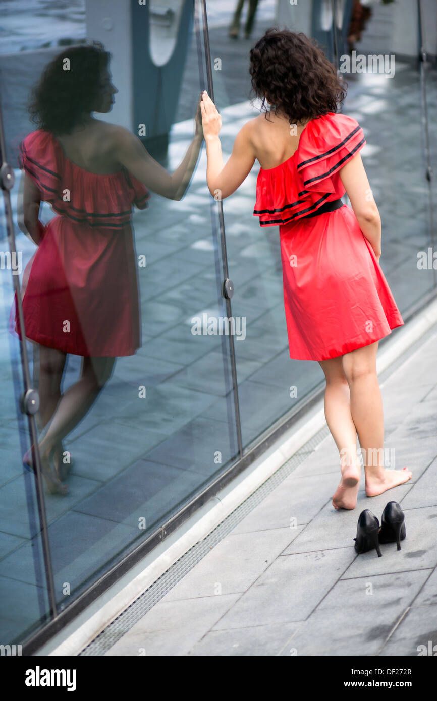 Woman in red dress walk along glass wall - Stock Image