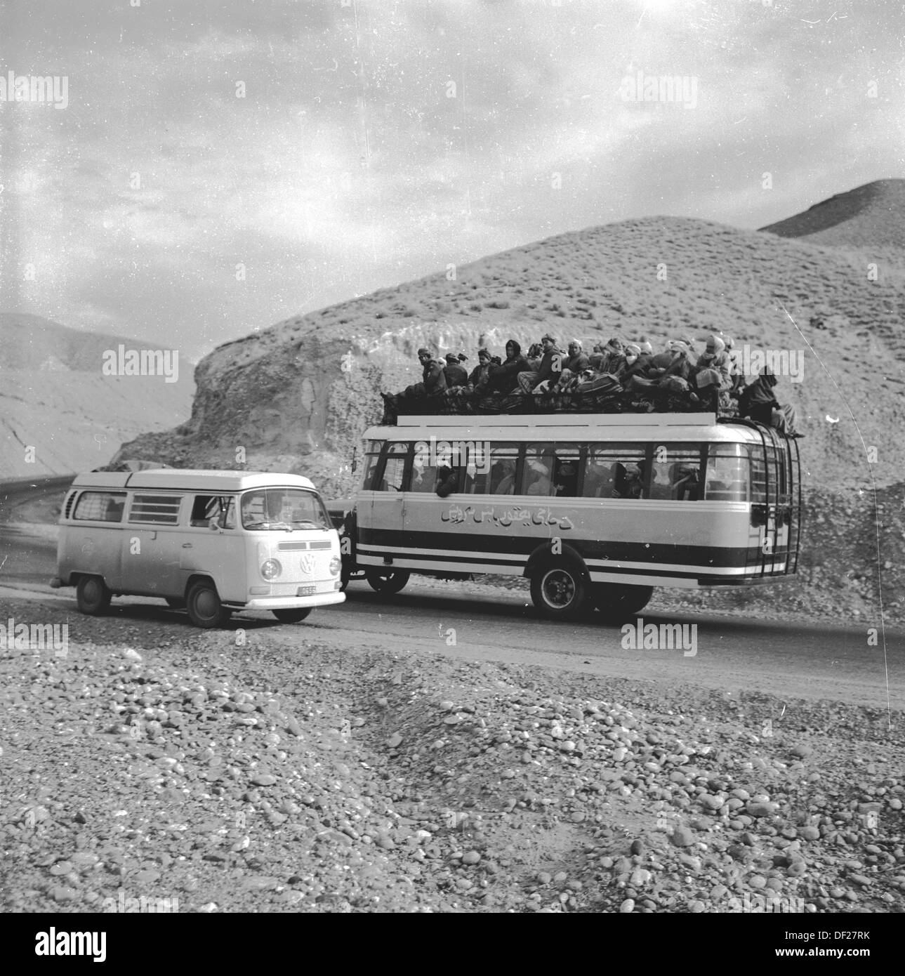 Historical picture from the1950s showing a fully loaded Afghan bus - with passengers perched on the roof -  and a VW camper van passing on a rocky mountain road in Afghanistan. - Stock Image