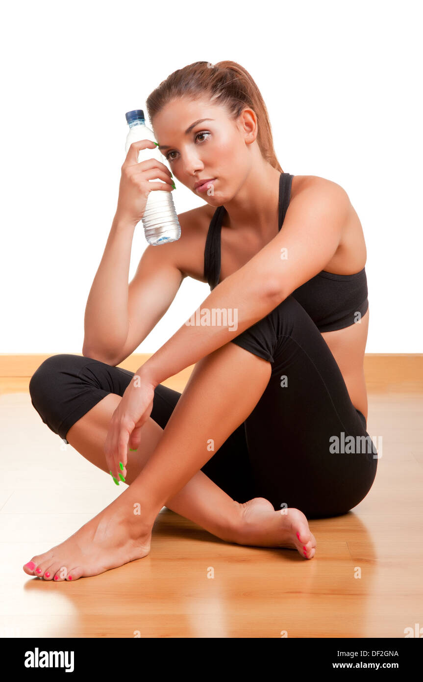 Woman holding a plastic bottle of water, dressed in sports clothes, sitting in a gym - Stock Image