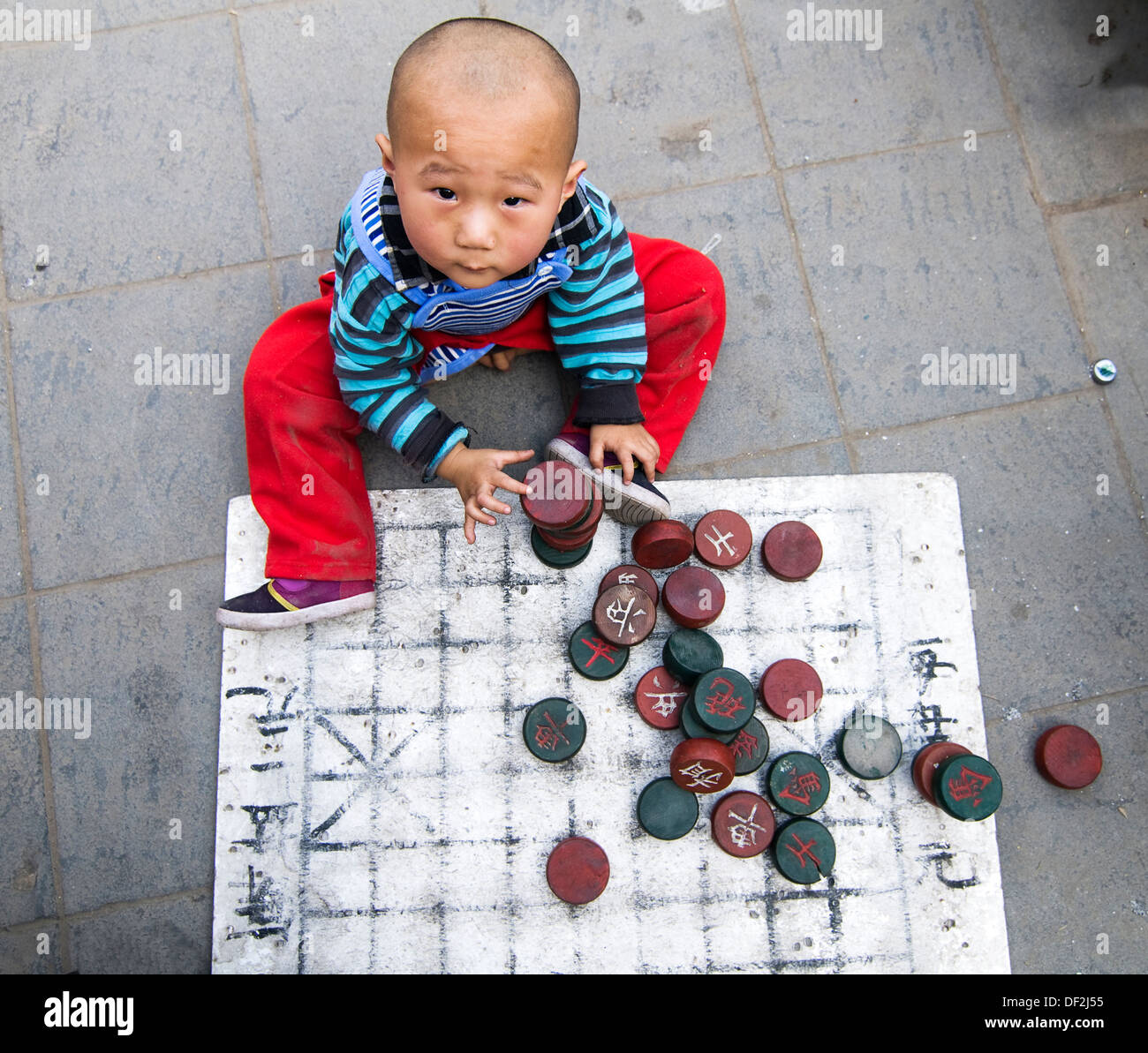 A boy playing with Xiangqi ( Chinese chess) board & soldiers. - Stock Image