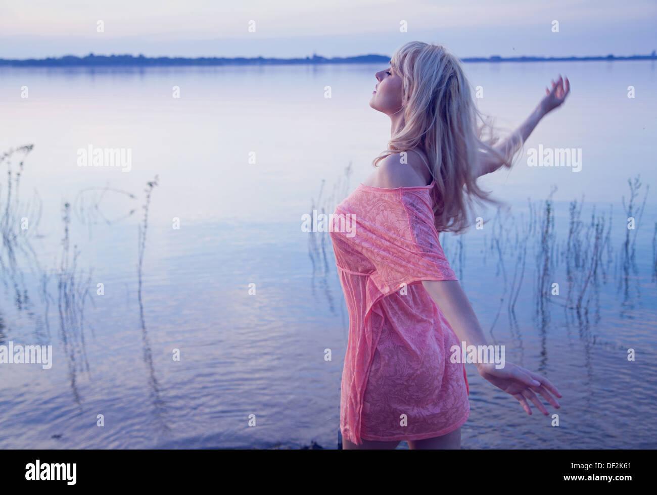 Art photo of blonde female model walking in the wather - Stock Image