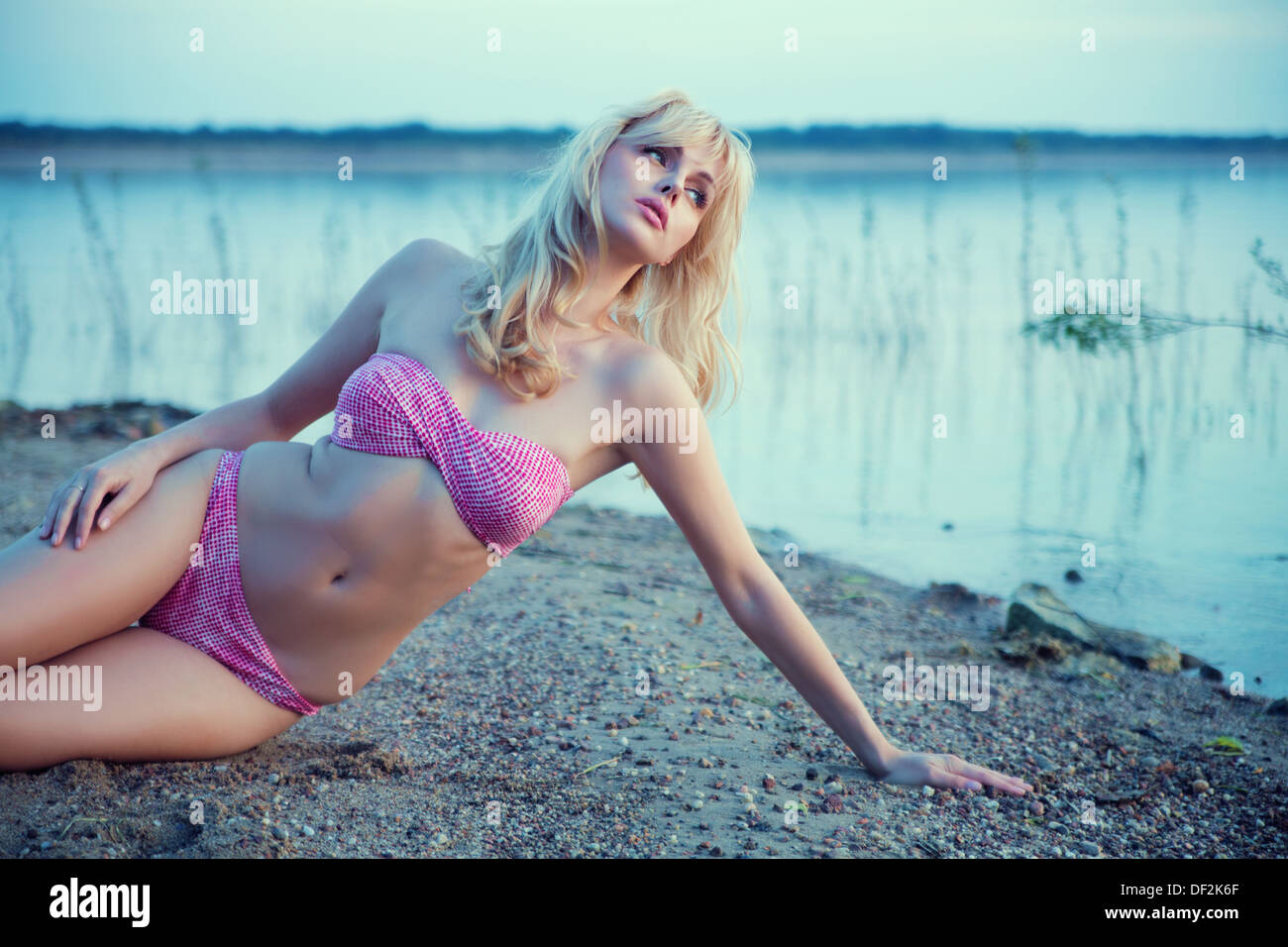 Portrait of blonde lady resting on the beach - Stock Image