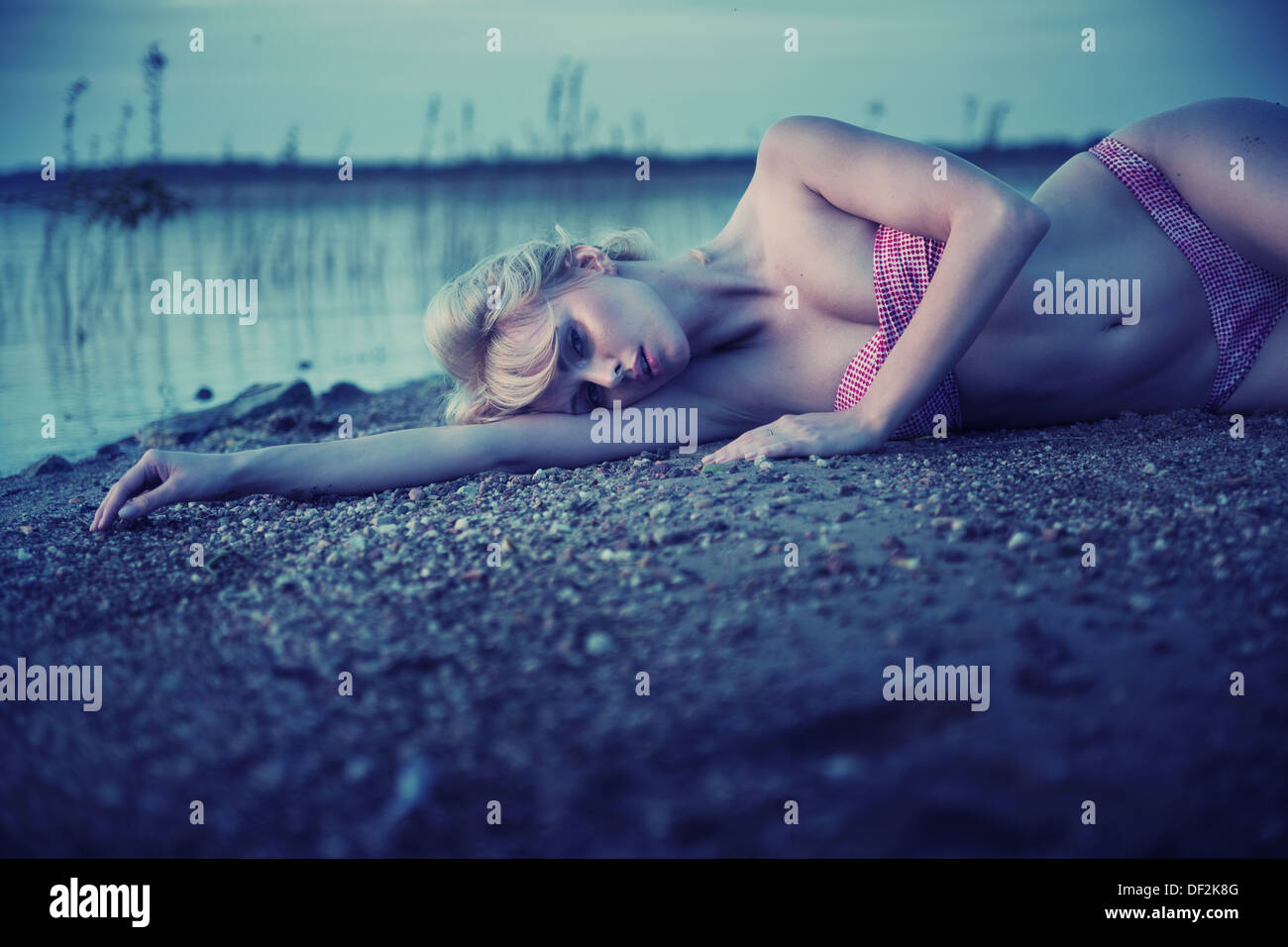Tired blonde woman lying on the beach - Stock Image