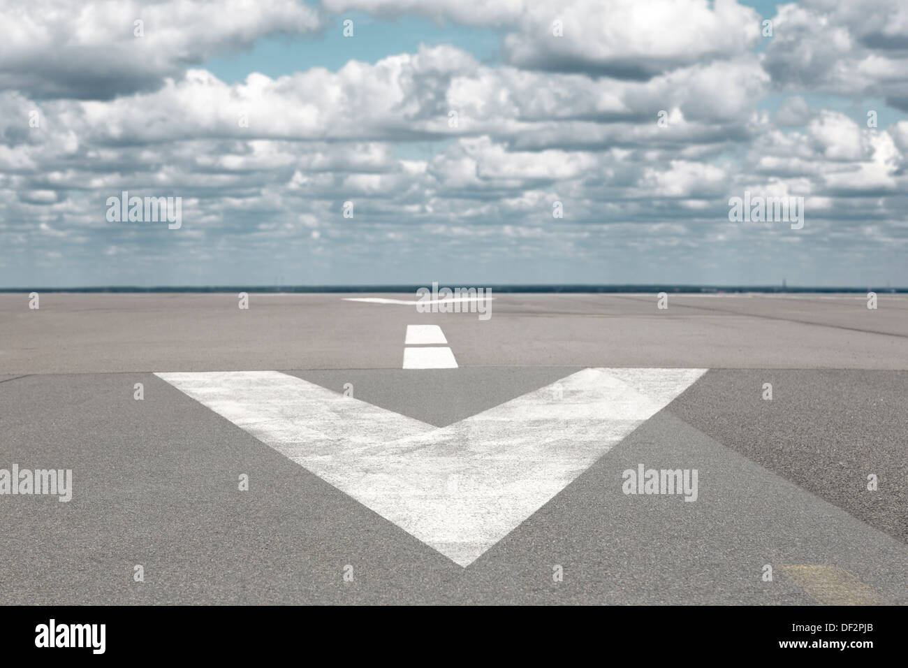 Runway airport with arrow and clouds - Stock Image