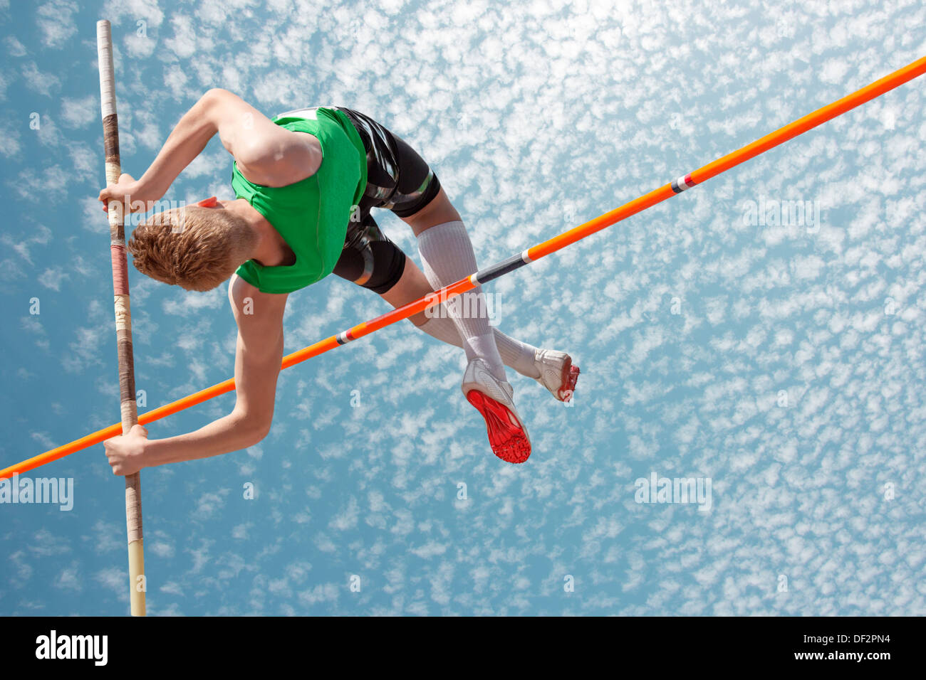 Young athletes pole vault seems to reach the sky - Stock Image