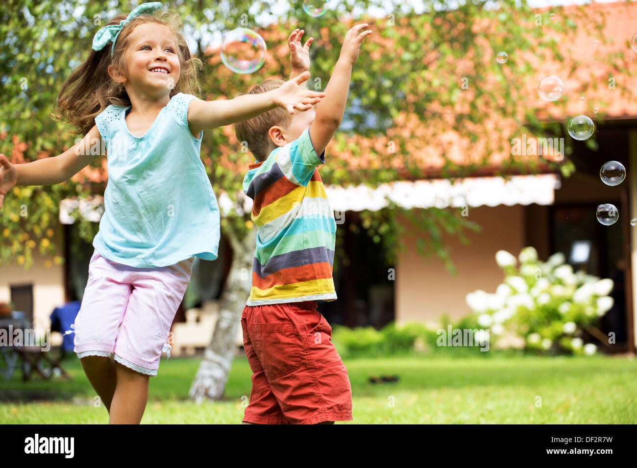 Cheerful children chasing the soap bubbles - Stock Image