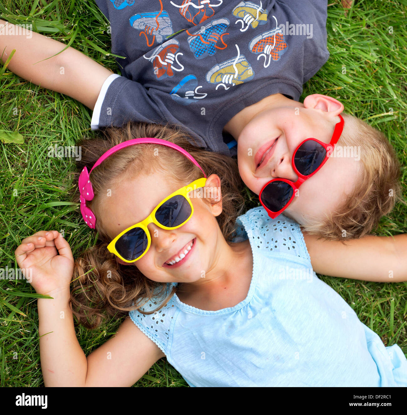 Picture presenting kids relaxing on the green grass - Stock Image