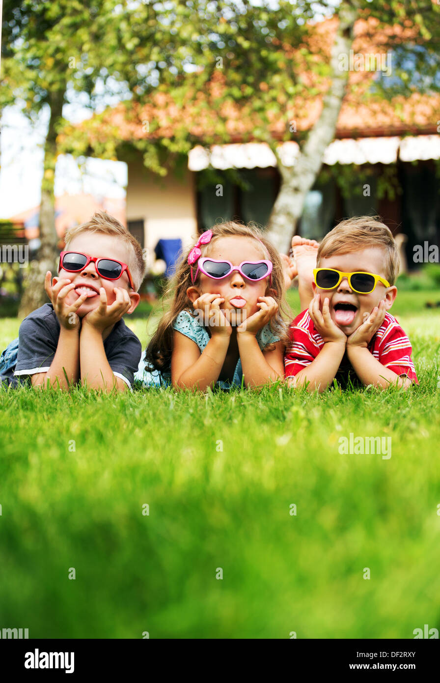Trio children showing their tongues - Stock Image