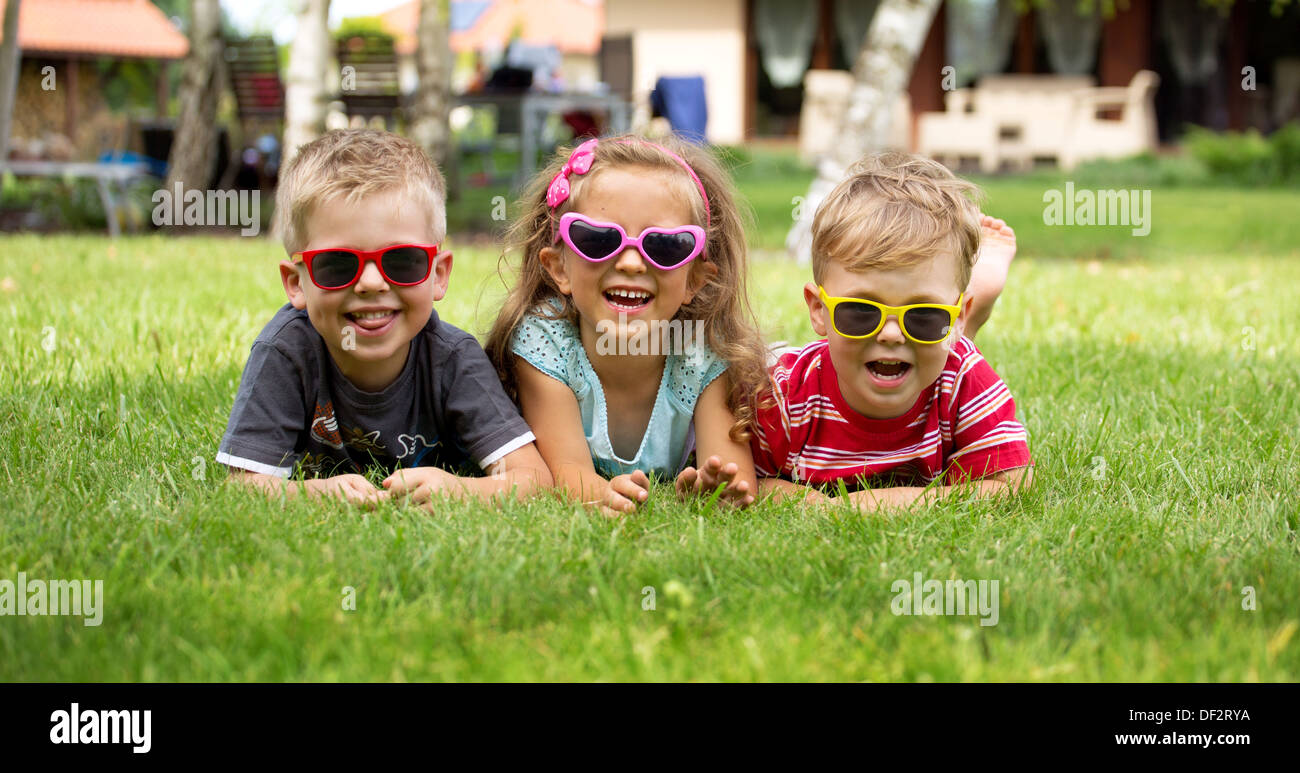 Happy laughing children lying on the grass - Stock Image