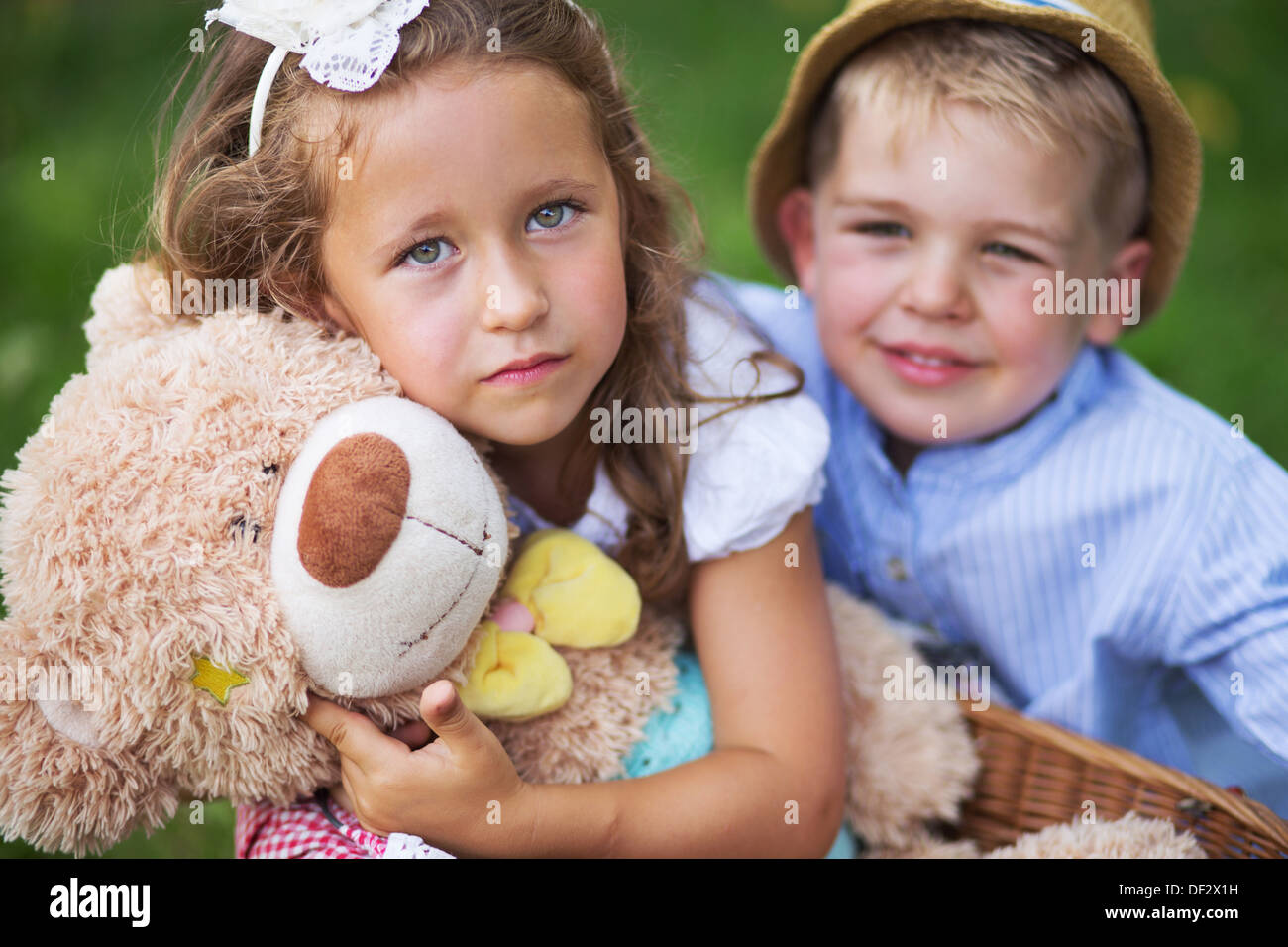 Glad kids holding cute teddy bear toy - Stock Image