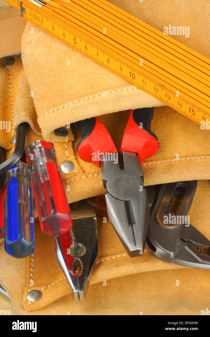 Manual worker tool set with some screwdrivers, metric ruler, pipe wrench and some pairs of pliers in a tool bag - Stock Image
