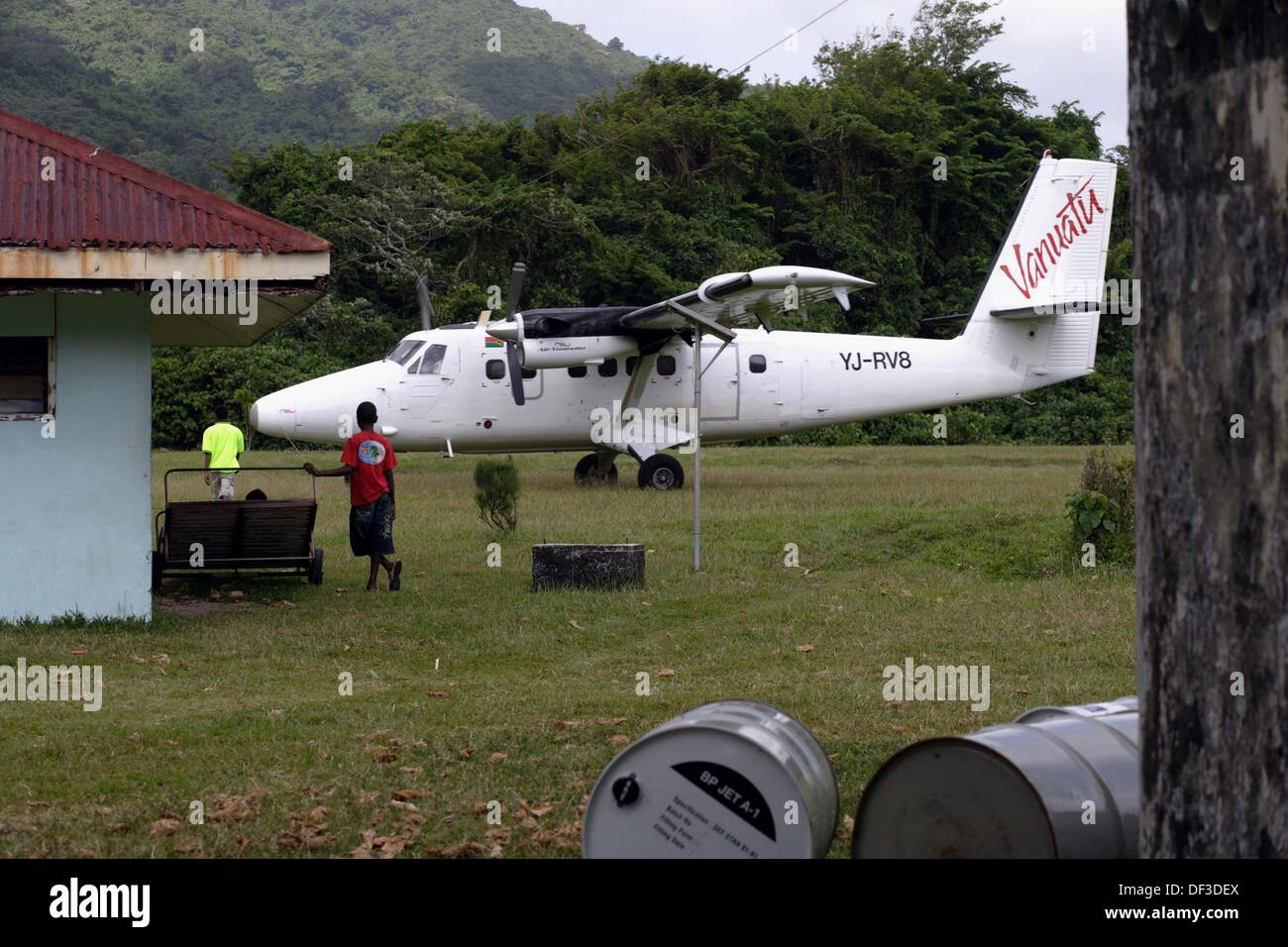A Twin Otter turboprop aircraft standing on the grass tarmac of the airport of Sola with fuel barrels, people and the small - Stock Image