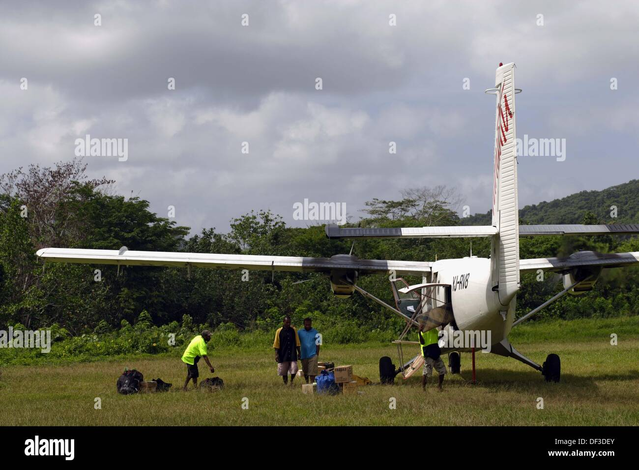 Men offloading and onloading luggage and cargo from a Twin Otter aircraft standing on the grass tarmc of the airport of Sola, - Stock Image