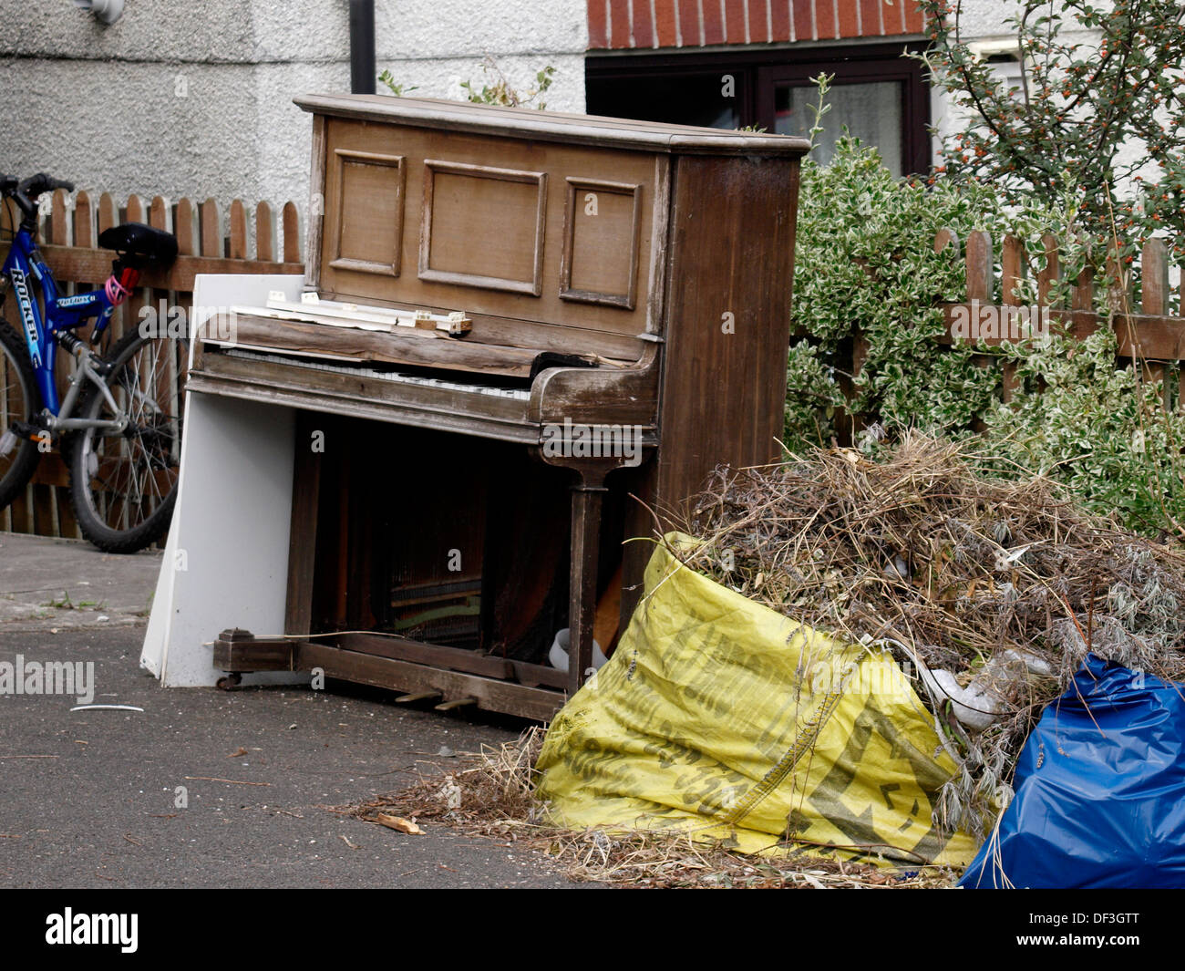 Old piano thrown out with the rubbish, Bude, Cornwall, UK 2013 - Stock Image