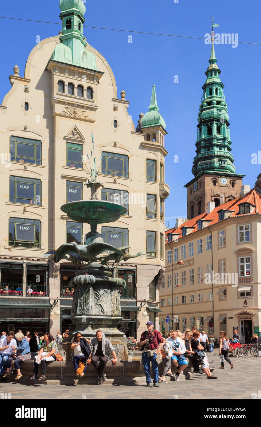 People by the Stork Fountain in Amagertorv Square with old buildings and St Nikolaj Church tower Amager Torv, Copenhagen Denmark - Stock Image
