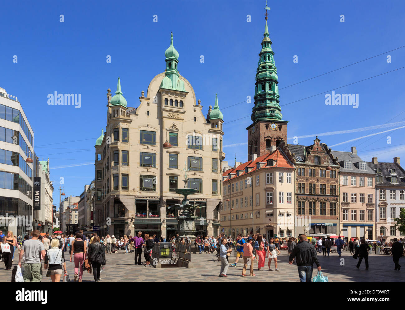 Amagertorv Square with old city buildings around the Stork Fountain and St Nikolaj Church tower Amager Torv, Copenhagen Denmark - Stock Image