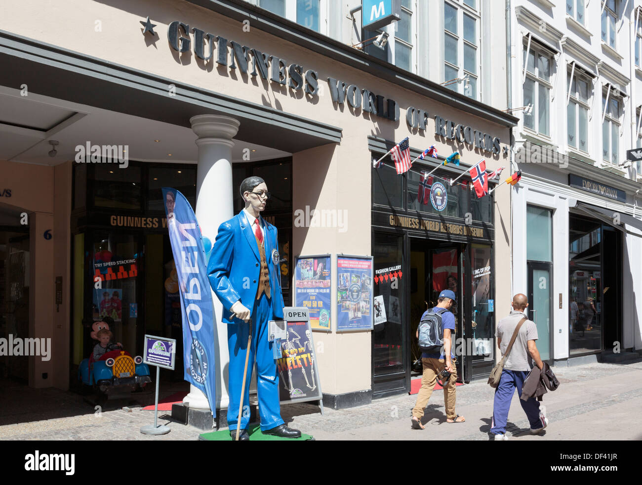 Two people by figure of world's tallest man outside Guinness World of Records museum in Stroget street, Copenhagen, Denmark - Stock Image