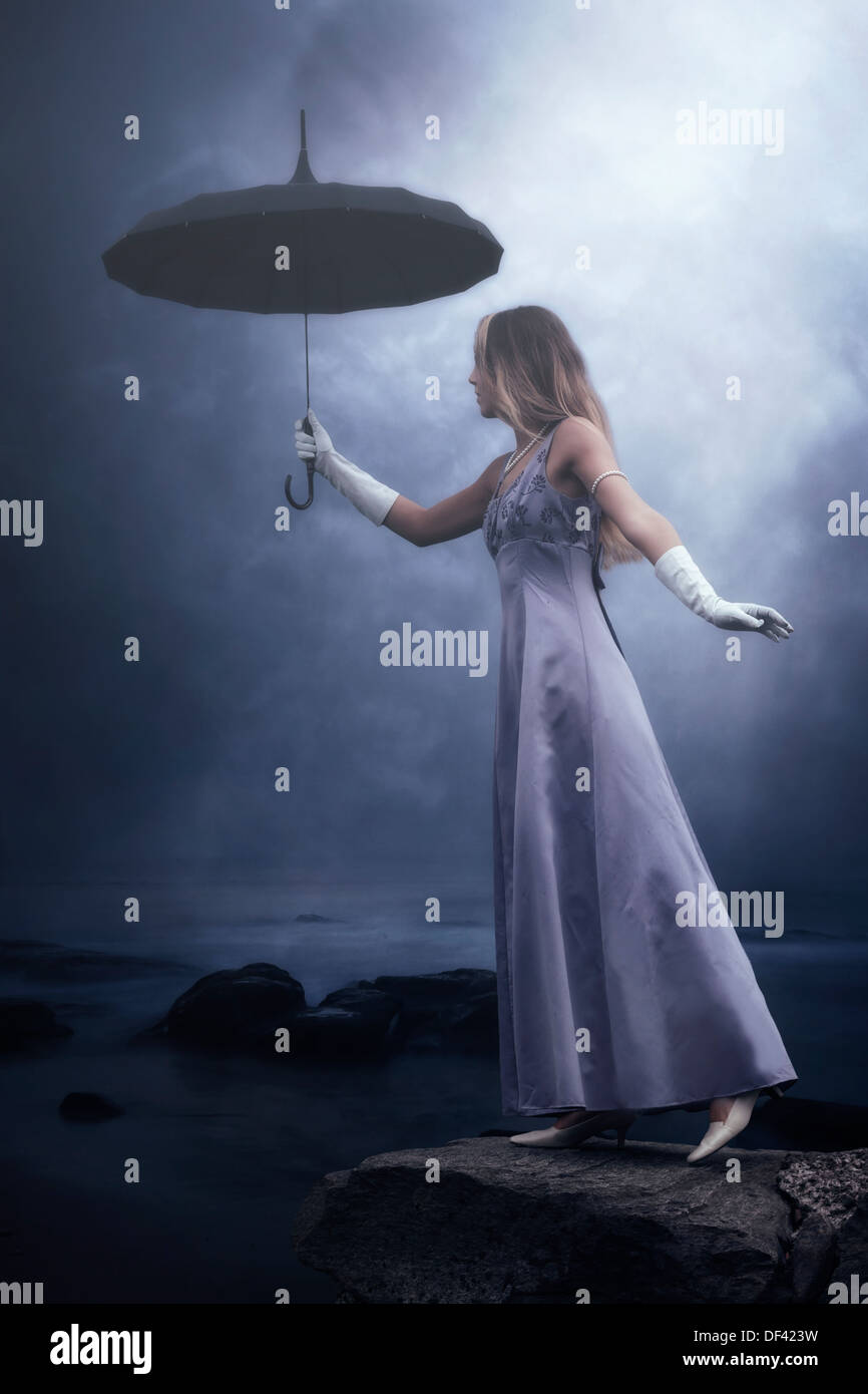 a woman in a purple dress is standing at a lake with a black umbrella in the rain - Stock Image