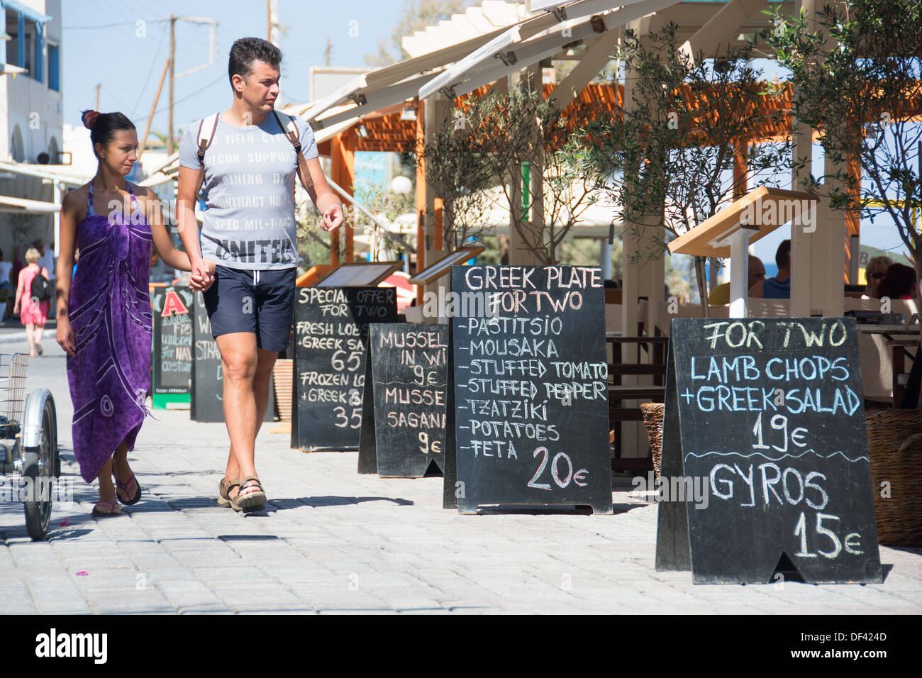 SANTORINI (THIRA), CYCLADES, GREECE. Holidaymakers walking past a taverna with blackboards advertising meal deals for two. - Stock Image