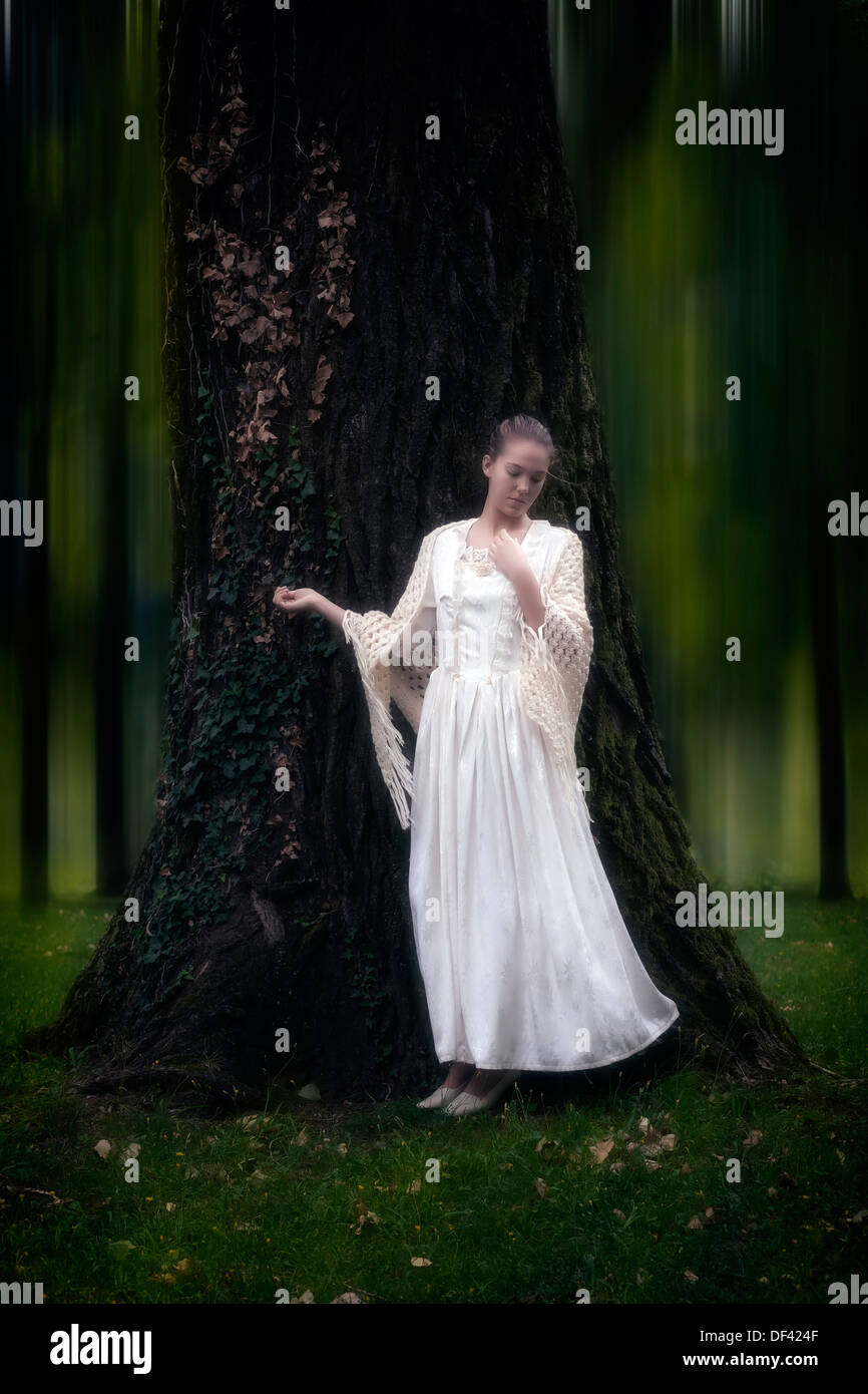 a girl in a period dress is leaning at a tree - Stock Image