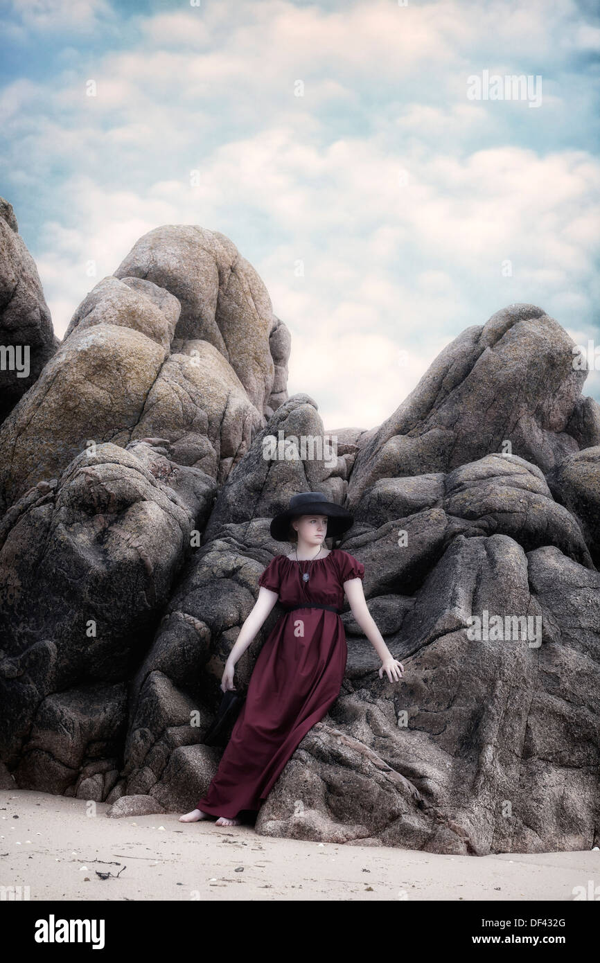 a young girl in a red dress with a black sunhat is leaning against rocks at the beach - Stock Image
