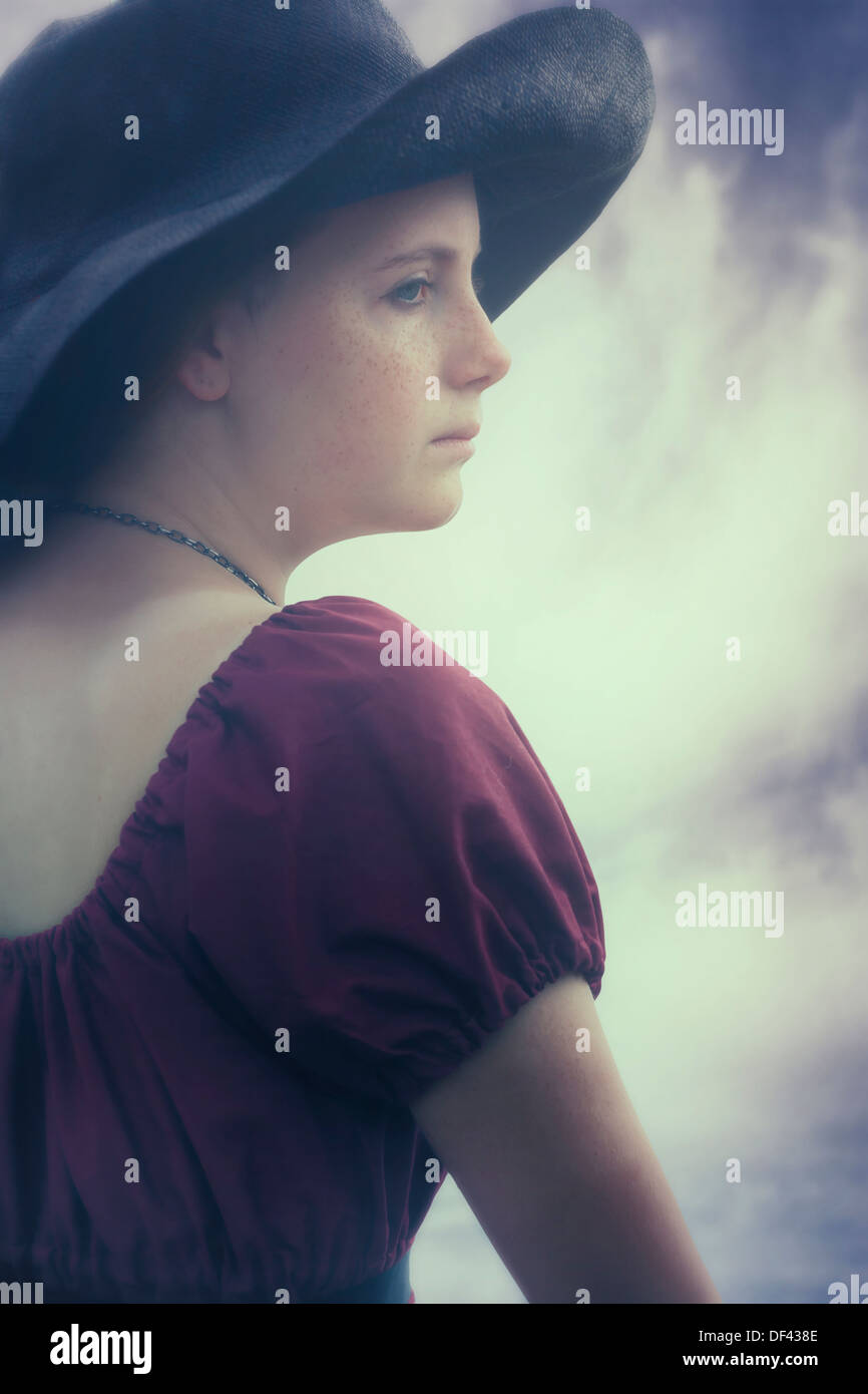 a sad young girl with black sunhat - Stock Image