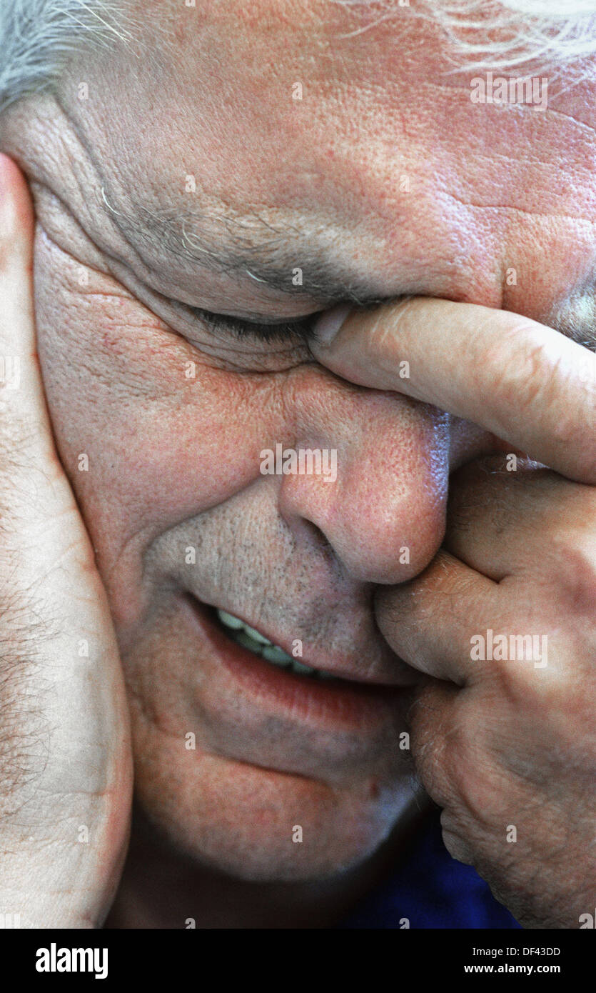 Male exhibiting symptoms of anguish, headaches and stress - Stock Image