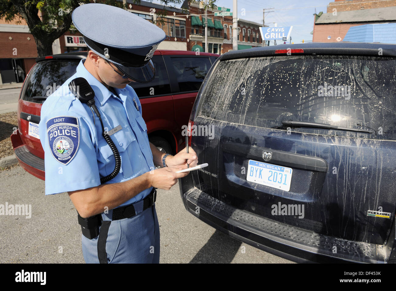 Police officer writes a ticket for parking violation - Stock Image