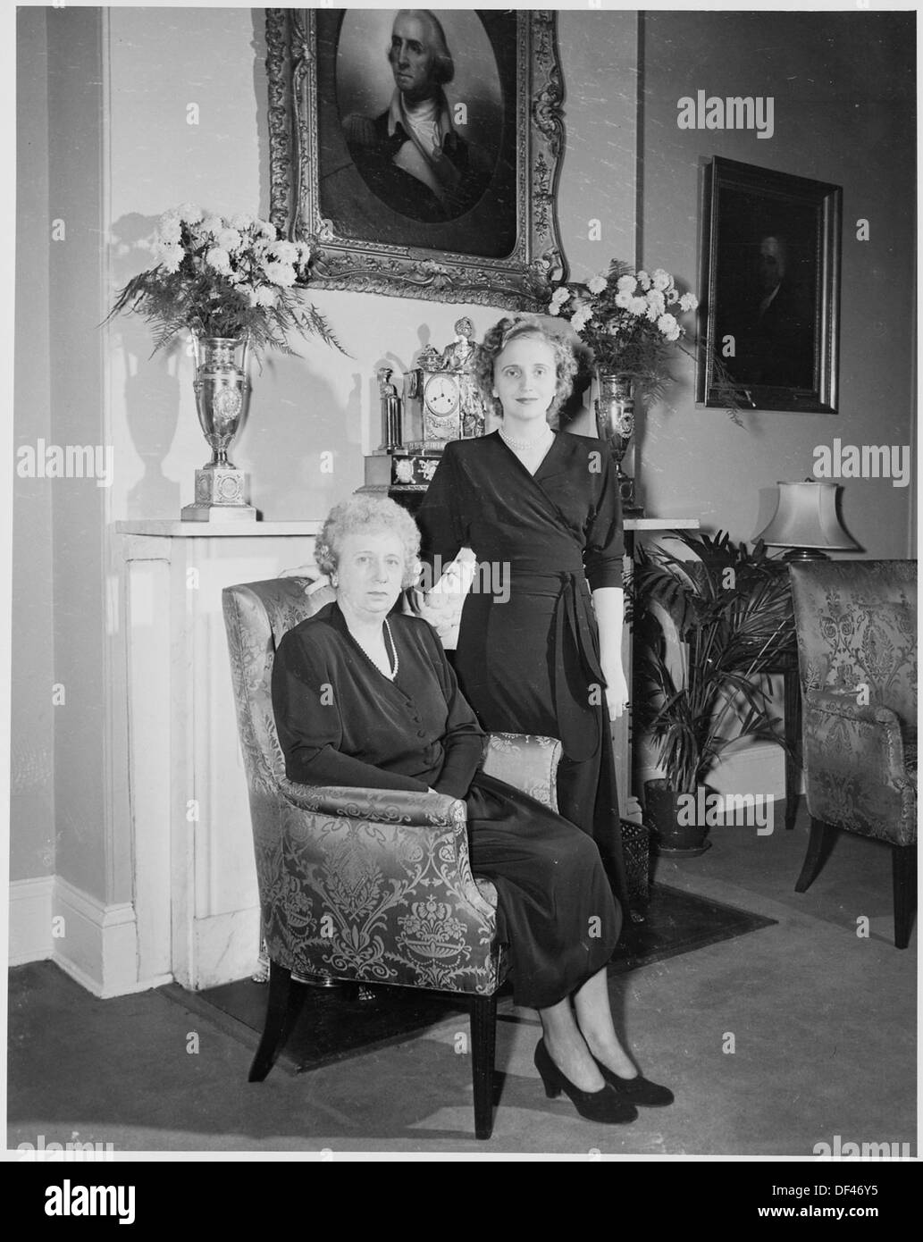First Lady Bess Truman poses with her daughter, Margaret, for a portrait photograph in front of the fireplace at... 200024 - Stock Image