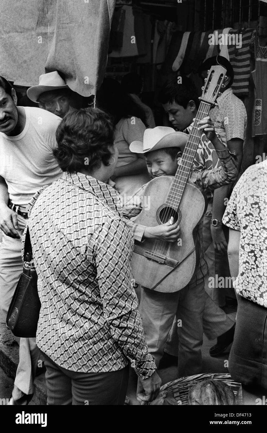 Mazatlan Mexico, young boy busking in the street. 1970s  1973 HOMER SYKES - Stock Image