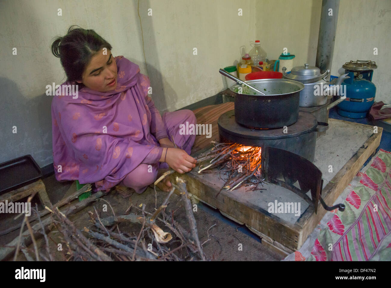 Young woman cooking on a fire inside of her house at Altit Village, near Karimabad, Hunza Valley, Gilgit-Baltistan, Pakistan - Stock Image