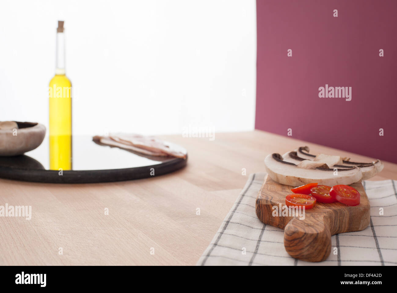 food preparation being carried out in a kitchen showing sliced mushrooms and tomatoes laying on a olive wood cutting board - Stock Image