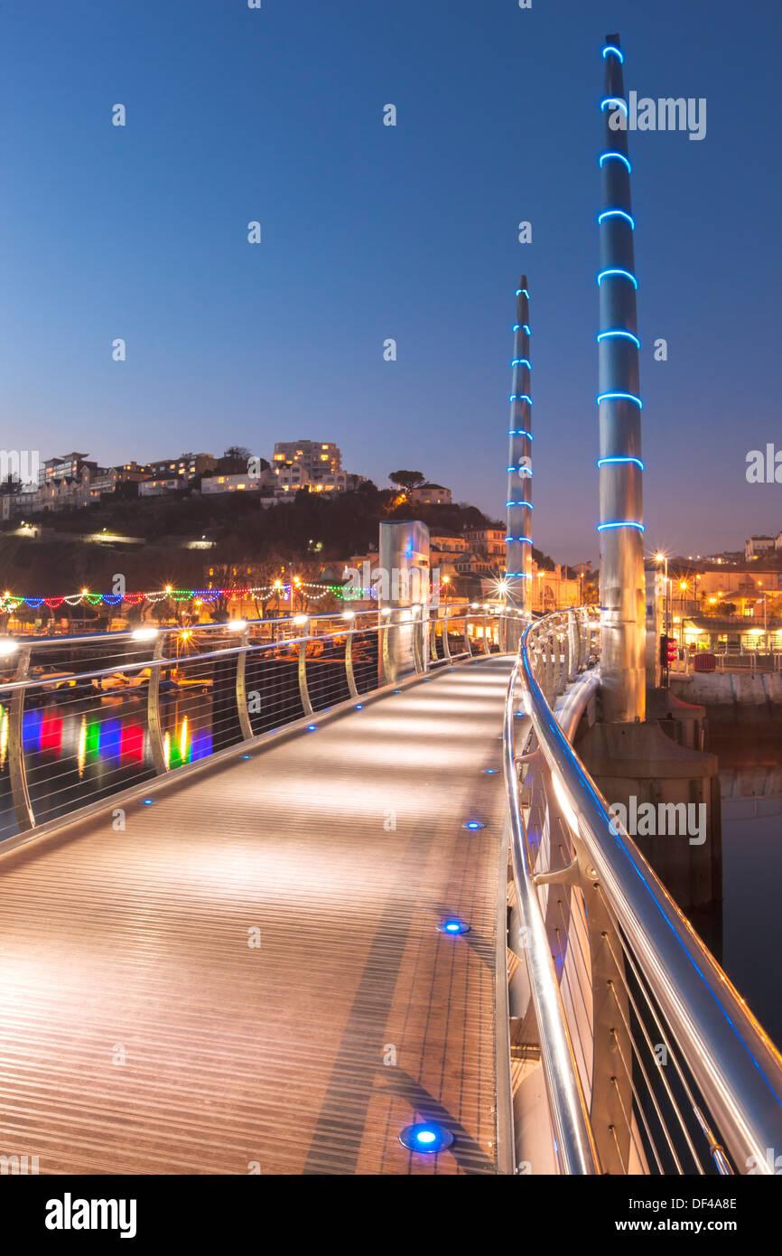 The modern Millenium Bridge at Torquay harbour, dusk. Stock Photo