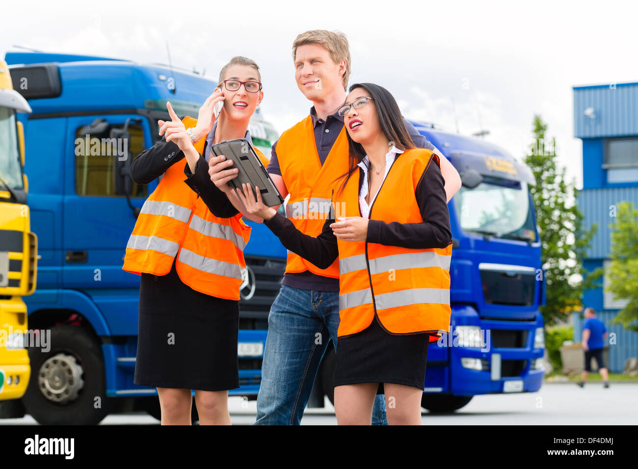 Logistics - proud driver or forwarder and colleagues with tablet computer, in front of trucks and trailers Stock Photo
