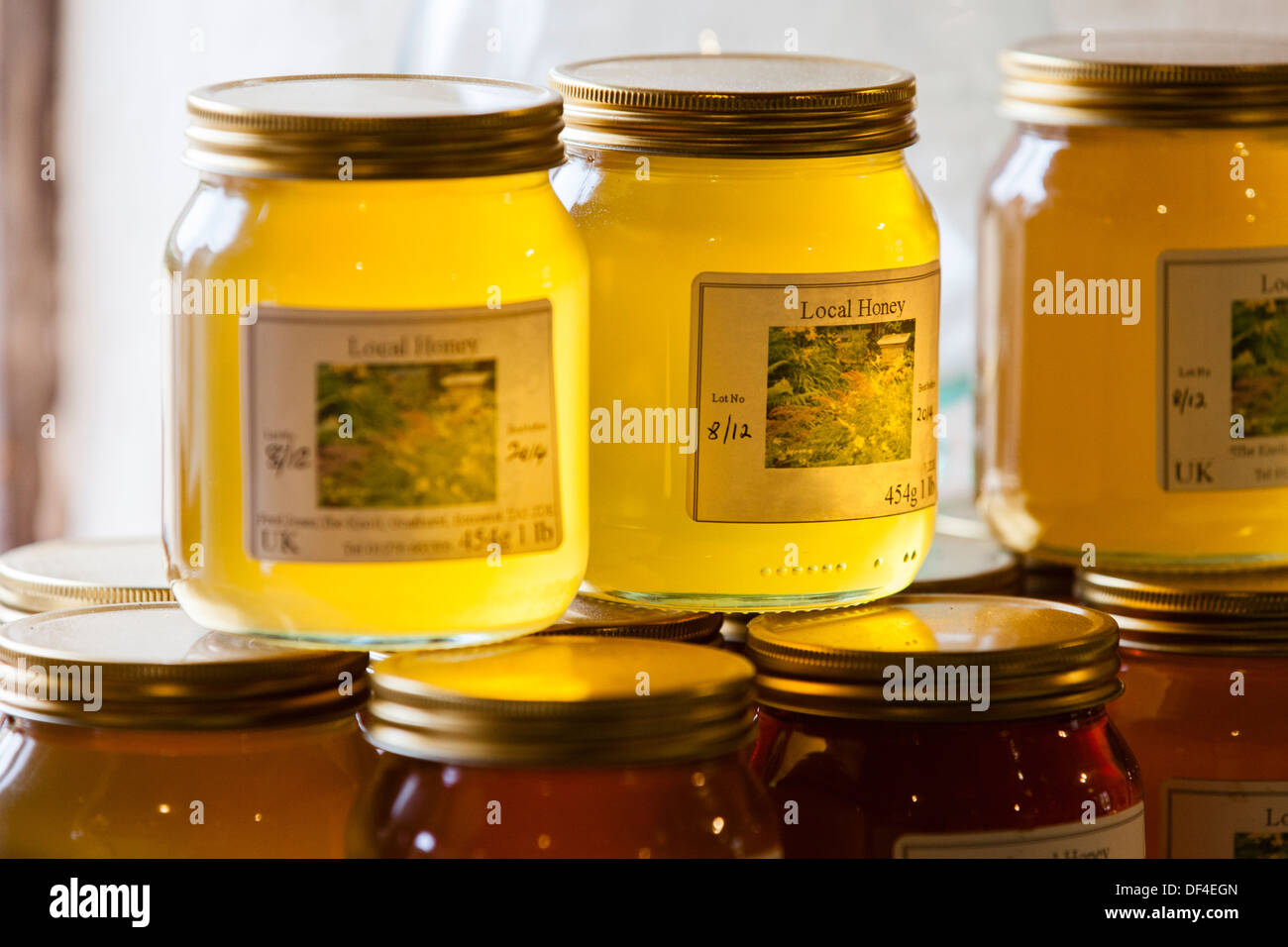 Jars of stacked Organic, home made honey on a window sill - Stock Image