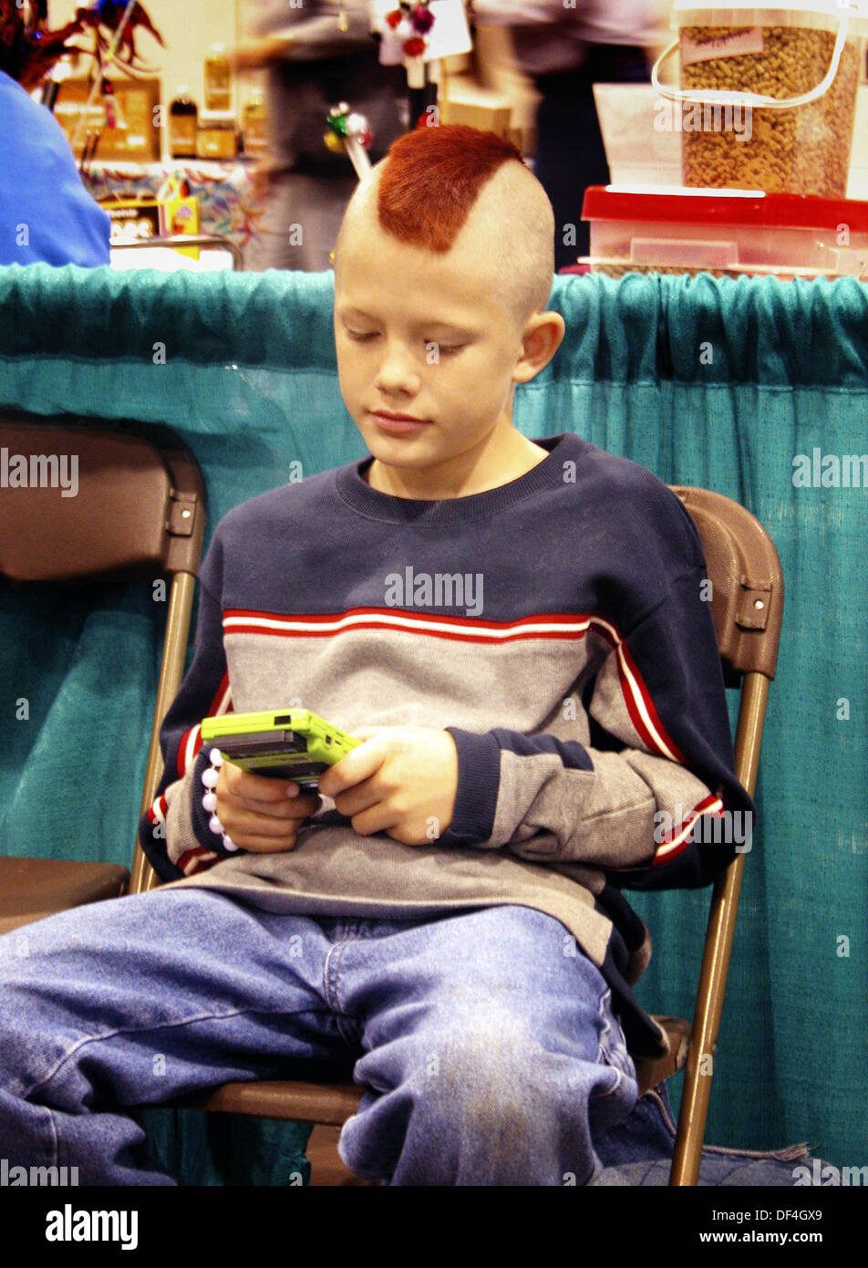 9 Years Old Boy Playing Gameboy With Mowhawk Haircut Stock Photo
