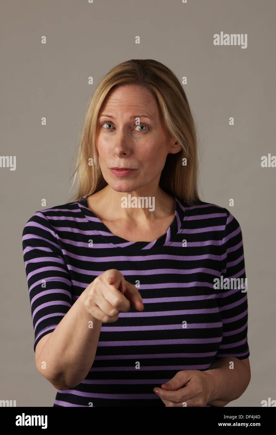 Stern and serious attractive middle aged woman pointing and