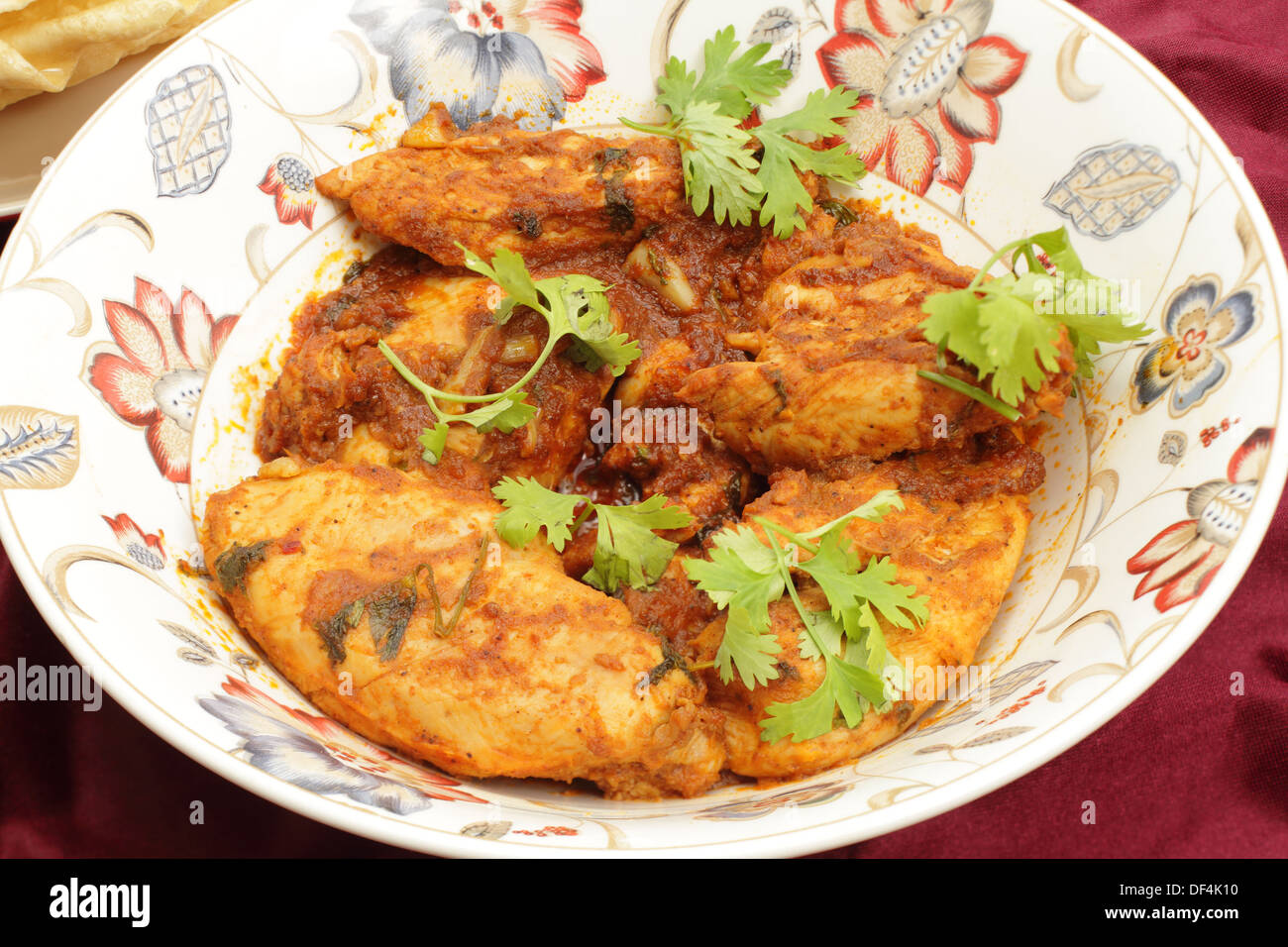 Kashmiri chicken - marinaded with spices and tomato sauce and fried with garlic and ginger -in a serving bowl - Stock Image