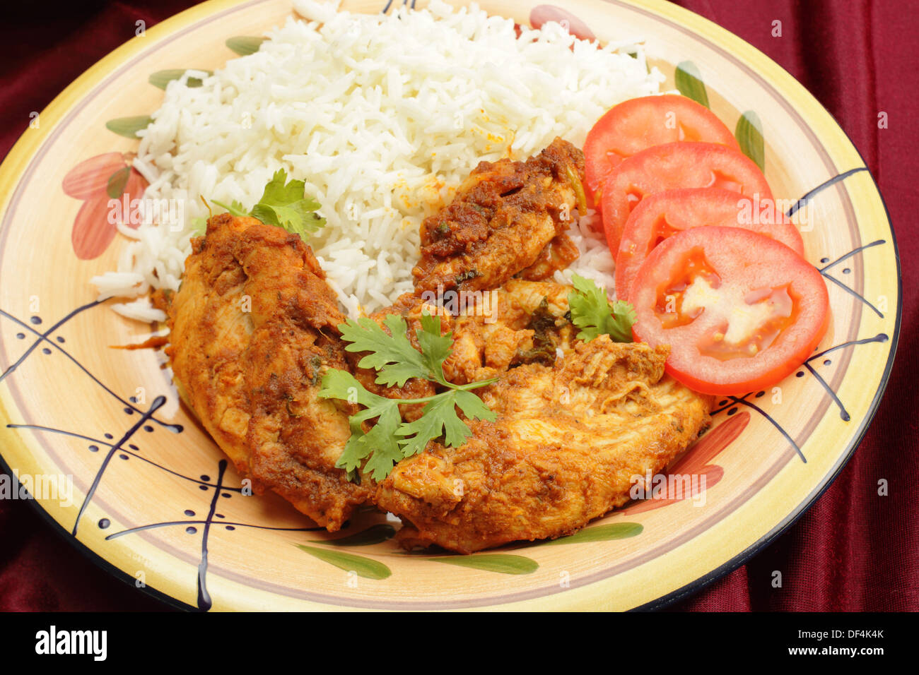 Kashmiri chicken, pieces of meat marinaded in spice mix and tomato ketchup, then fried with garlic and ginger - Stock Image