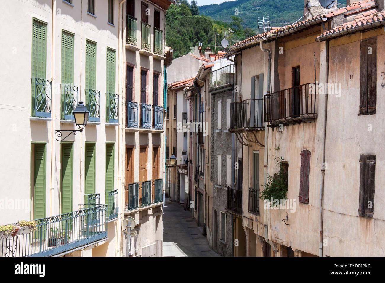 Multi-storey houses in narrow alleyway in Arles-sur-tech - Stock Image