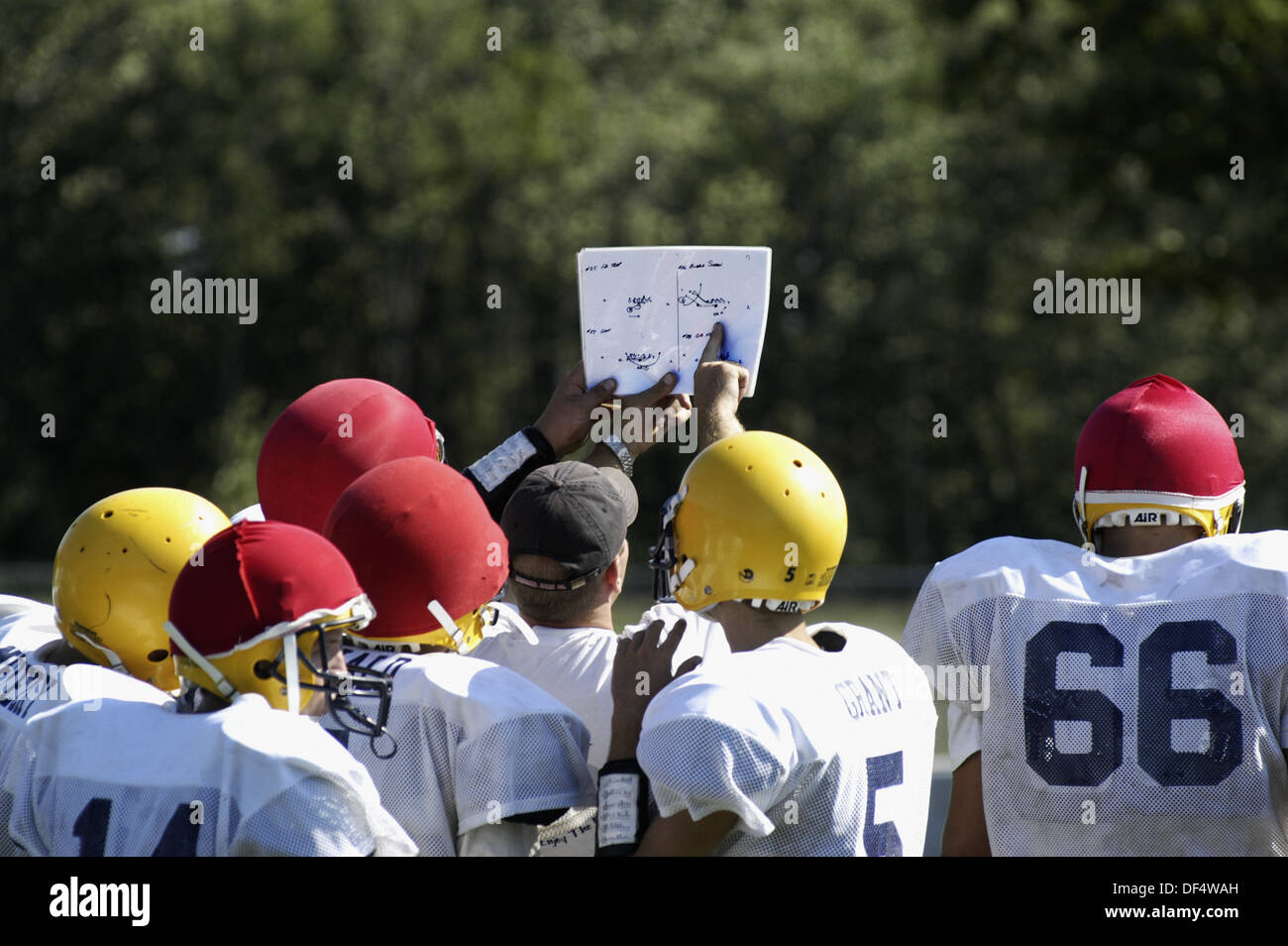 Football coach holds up play book for all players to see - Stock Image