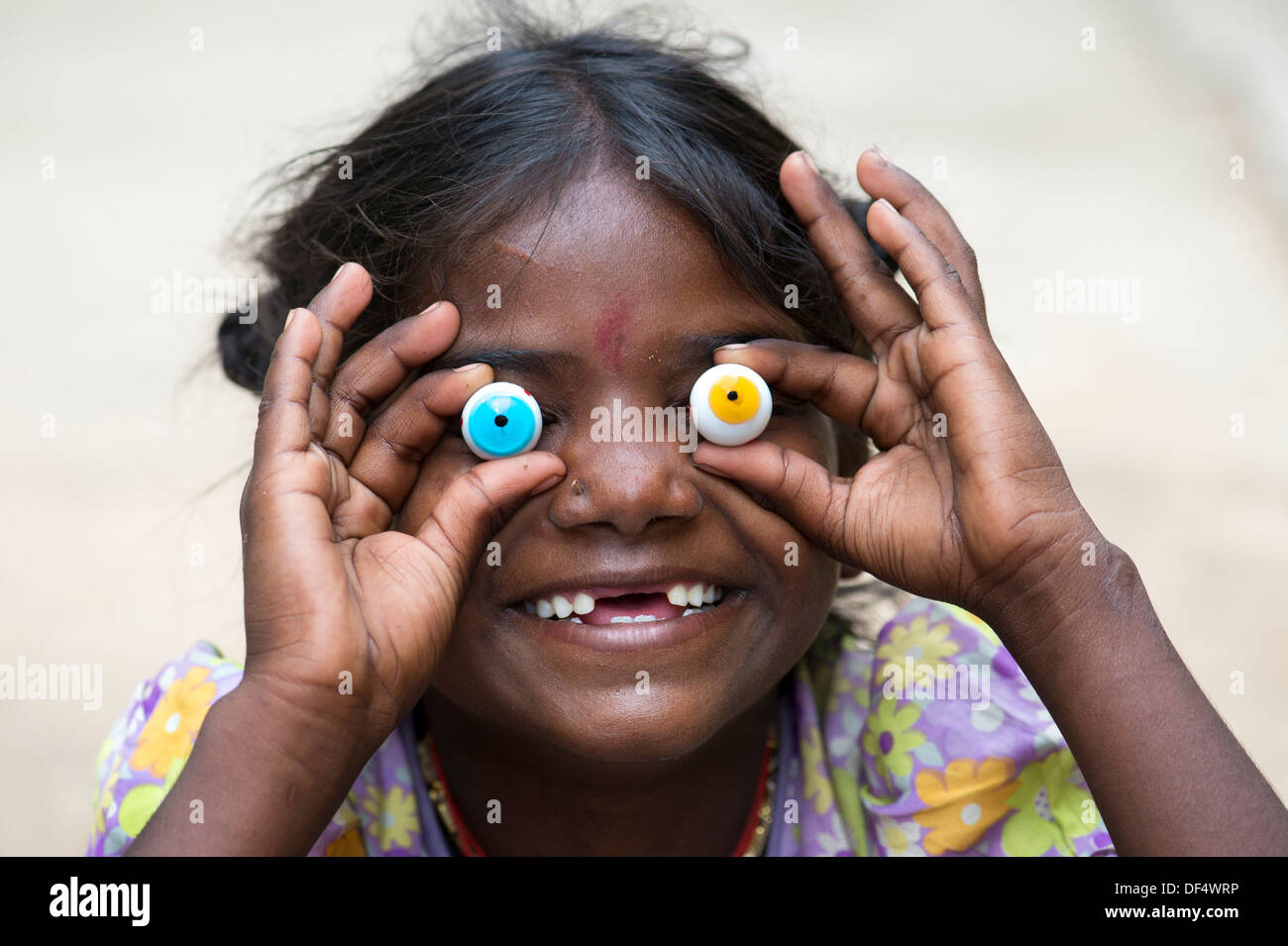 Poor happy funny Indian girl holding marble eyes with a toothless grin. India - Stock Image