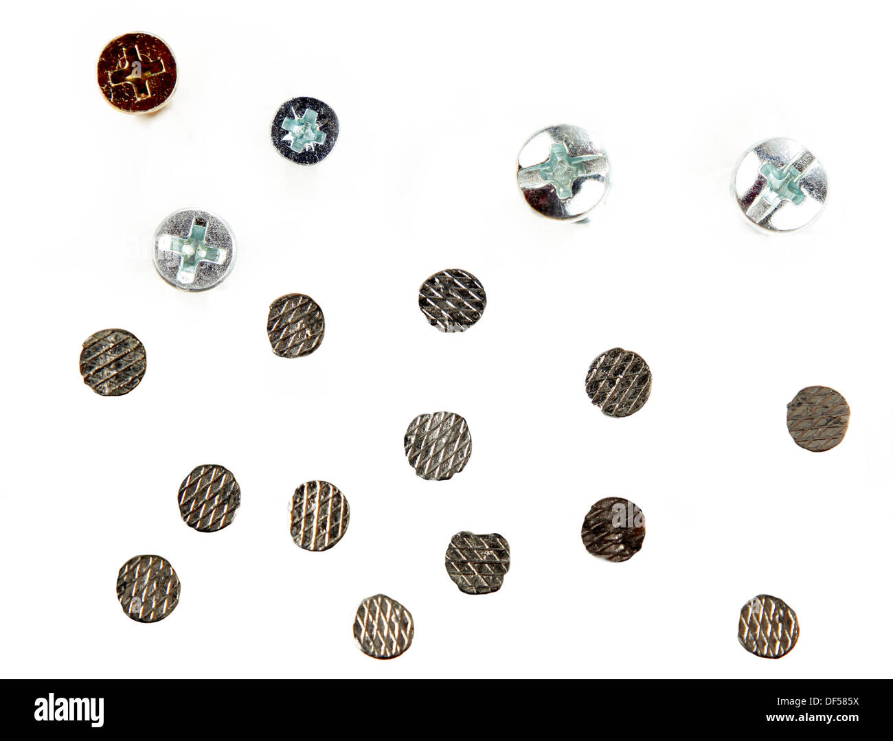Nail and screw heads on plain background - Stock Image